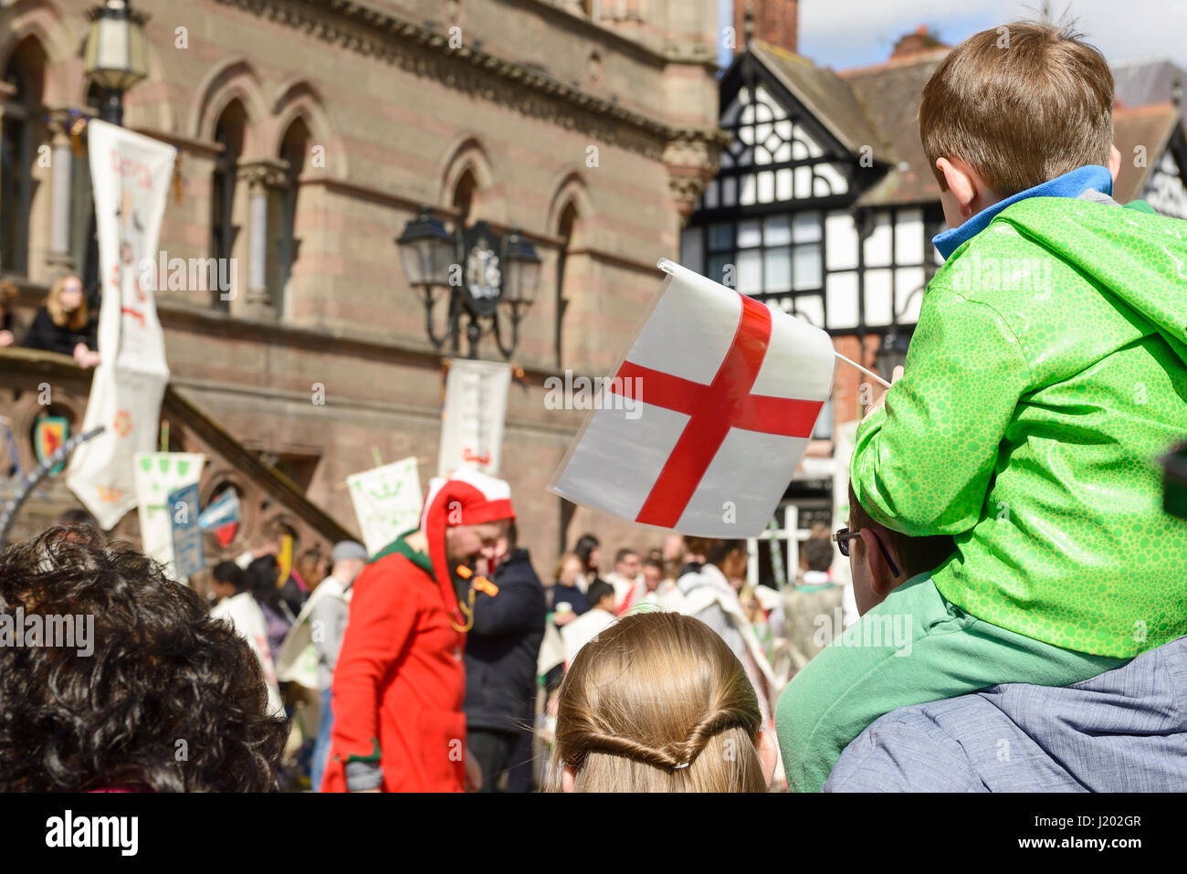 Chester, UK. 23rd April 2017. A boy with a flag watching the St George's day medieval street theatre performance - Stock Image