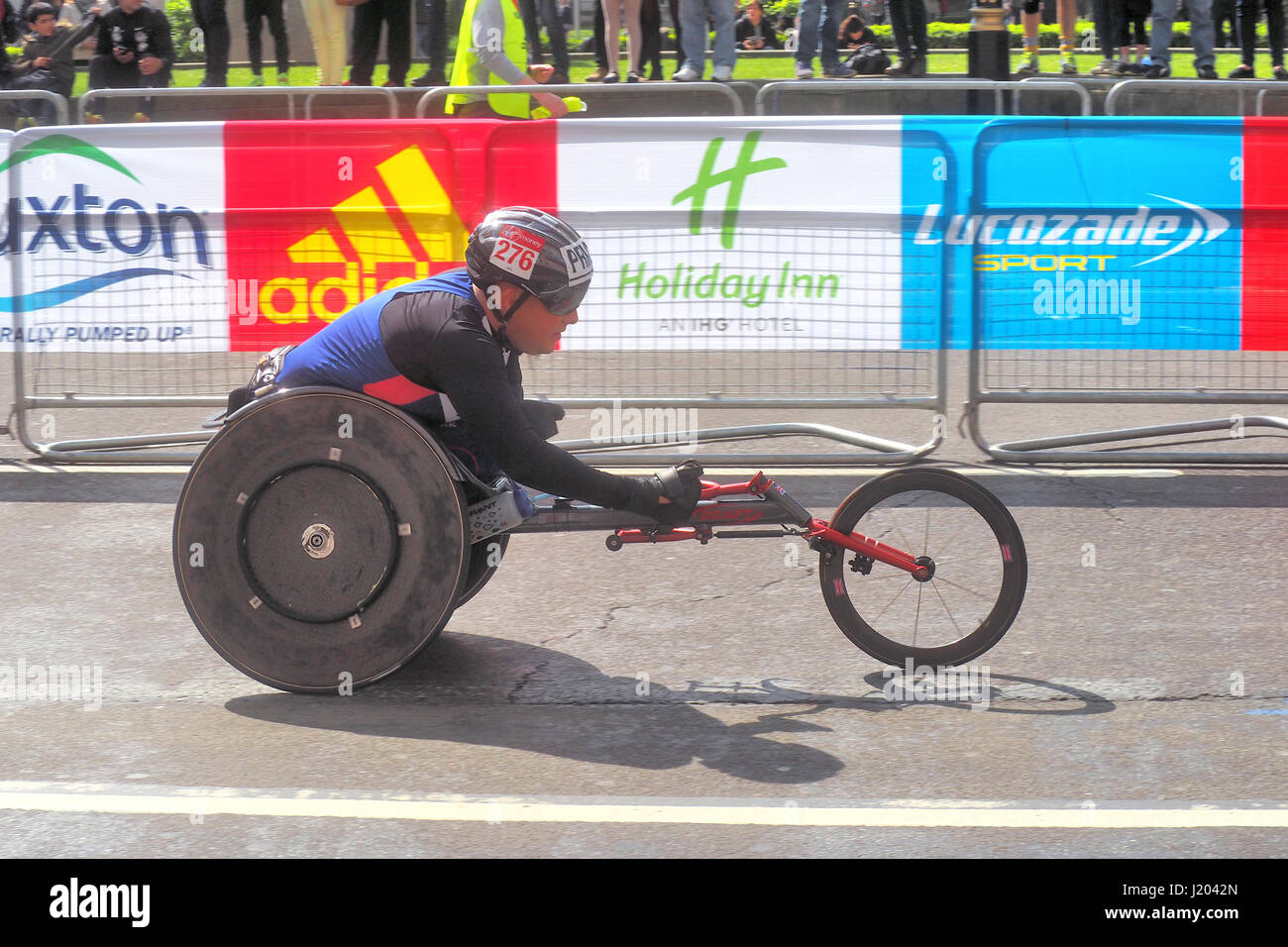 London, UK. 23rd Apr, 2017. A participant in the wheelchair section nears the finish line of the 2017 London marathon. Stock Photo