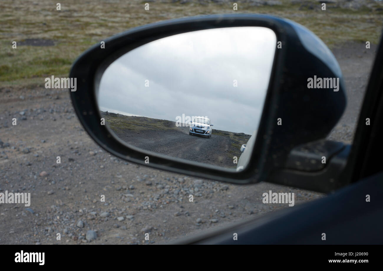 Reflection in car mirror of passing car on the lava dirt road in  Snaefellsjökull National Park, Iceland - Stock Image