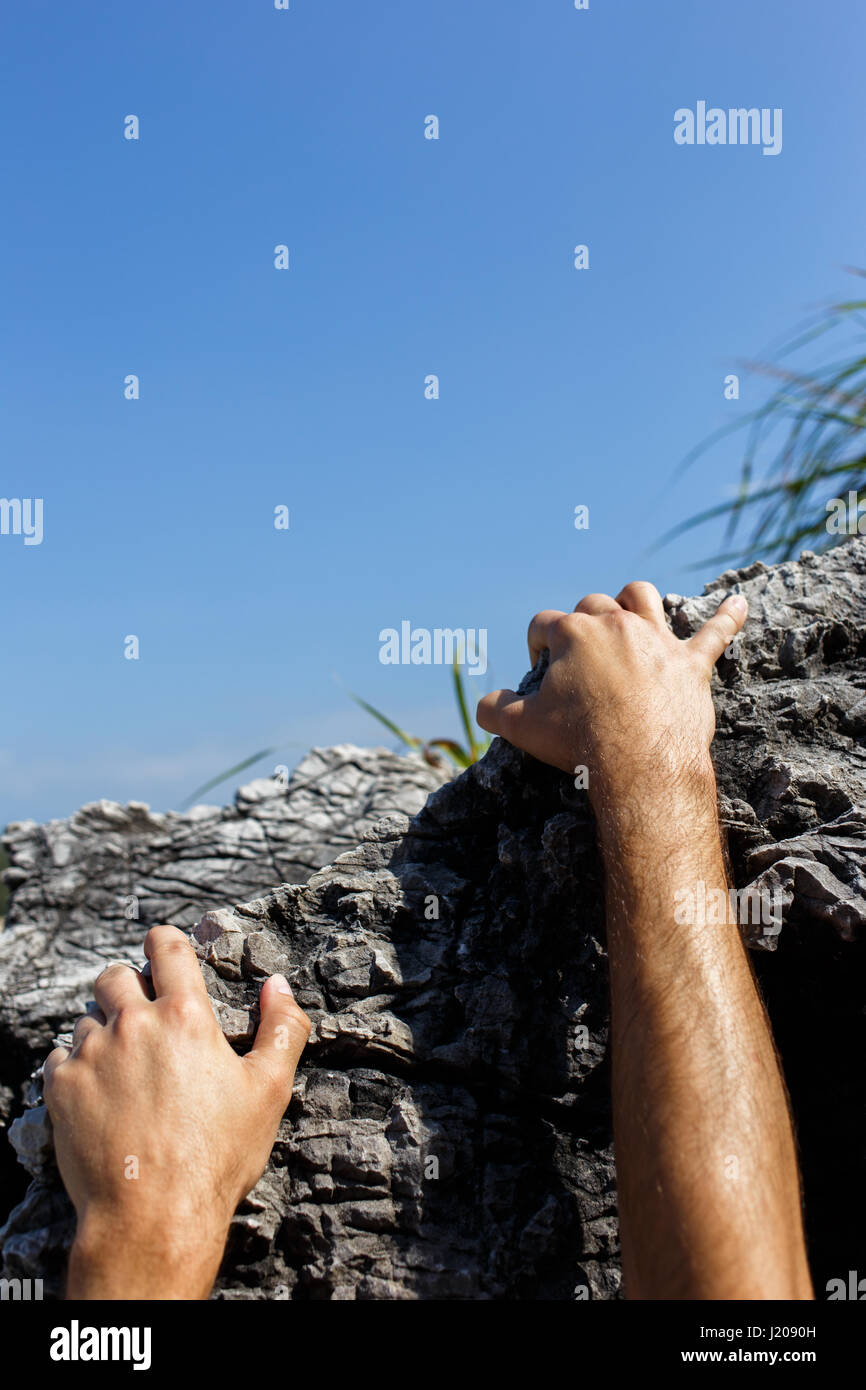 Man climbs on hill side Stock Photo