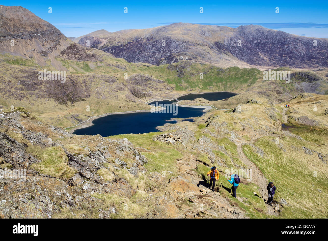 High view to Llyn Llydaw lake from slopes of Y Lliwedd in Snowdon Horseshoe with hikers hiking up on path in Snowdonia Stock Photo