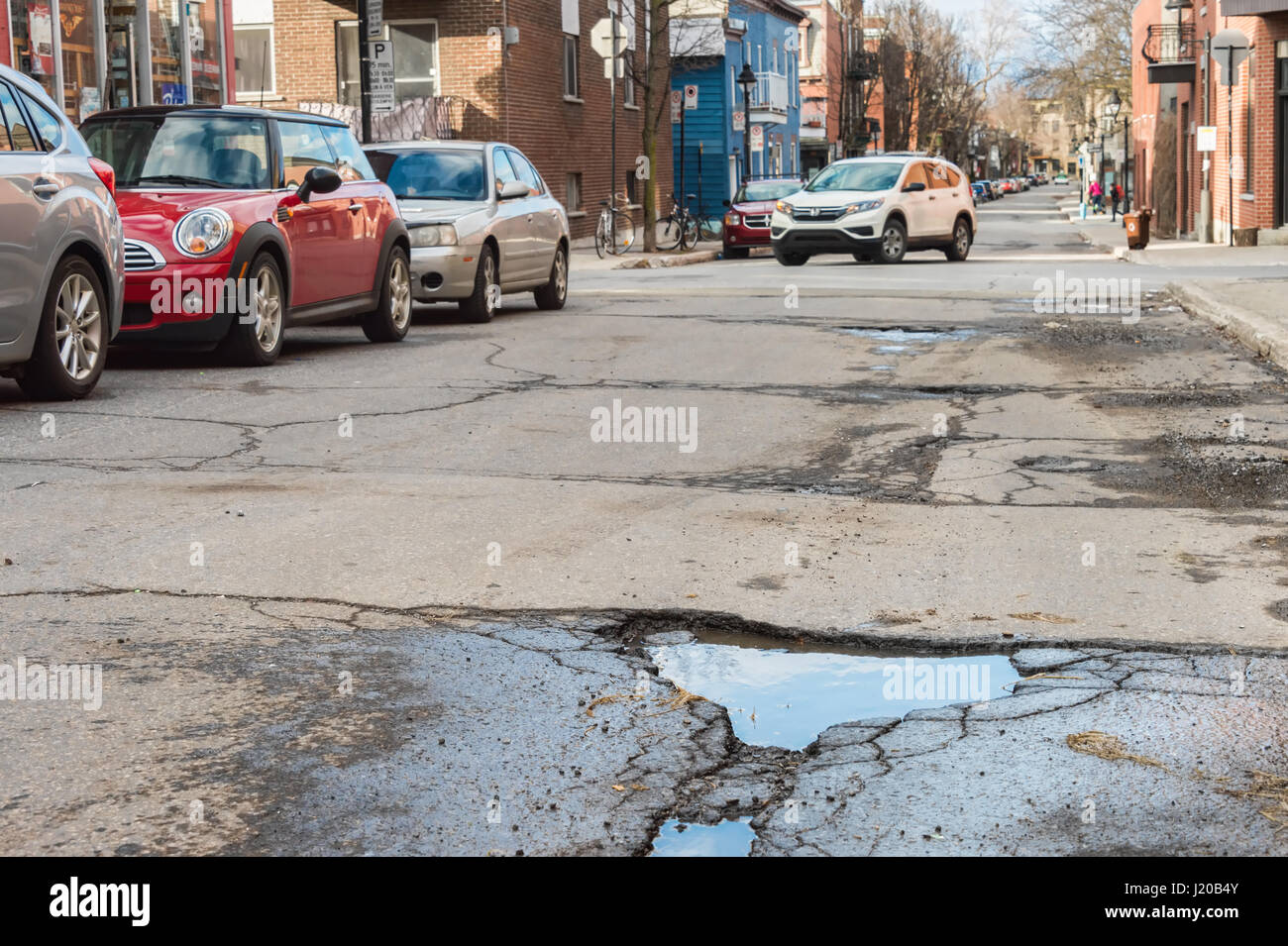 Montreal, Canada - 21 April 2017: Large unrepaired potholes on Bienville street - Stock Image