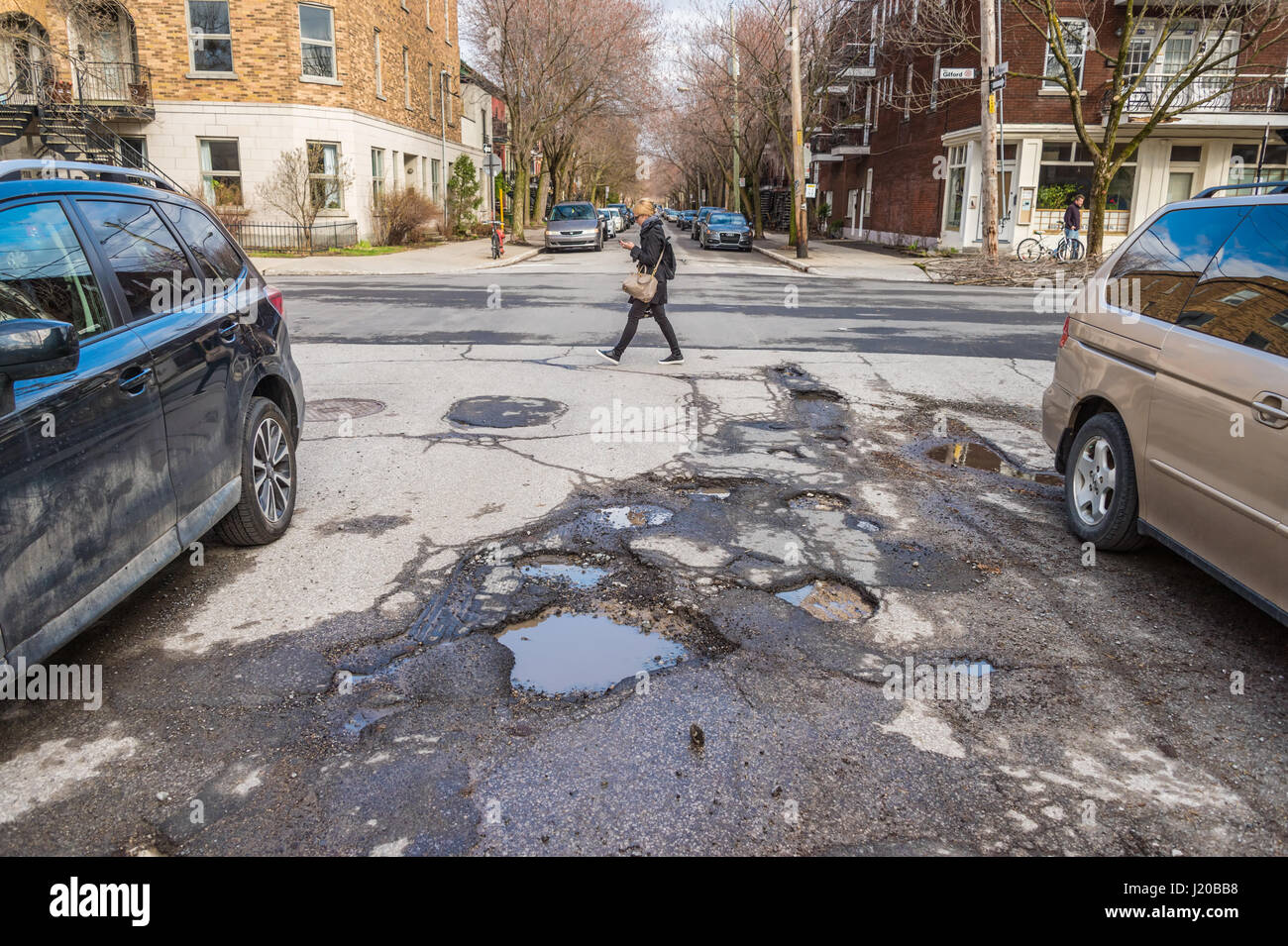 Montreal, Canada - 21 April 2017: Large unrepaired potholes on Boyer street - Stock Image