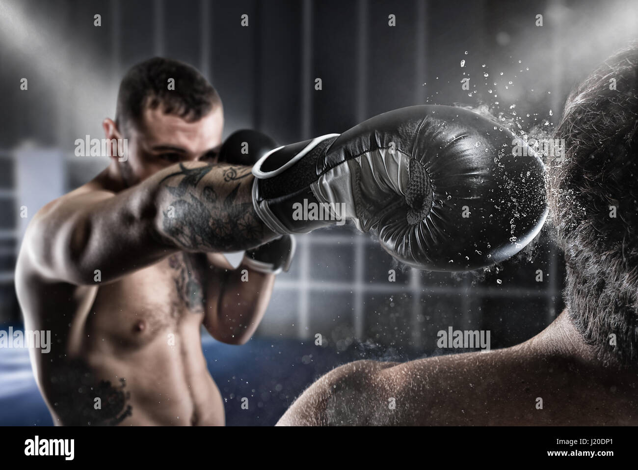 Boxer in a boxe competition beats his opponent - Stock Image
