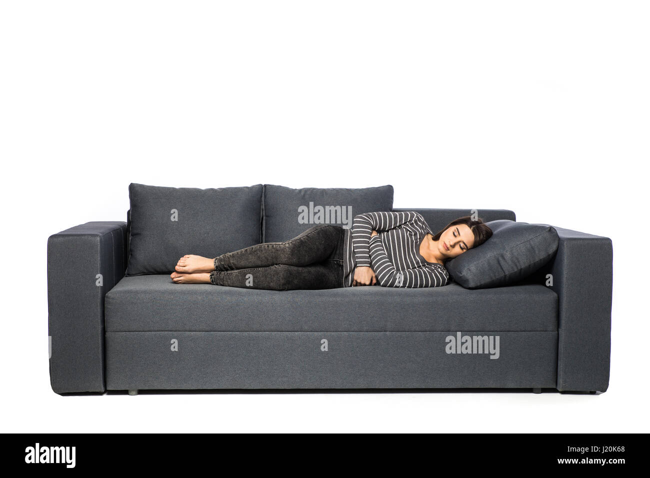 Woman lying on sofa looking sick in the living room - Stock Image