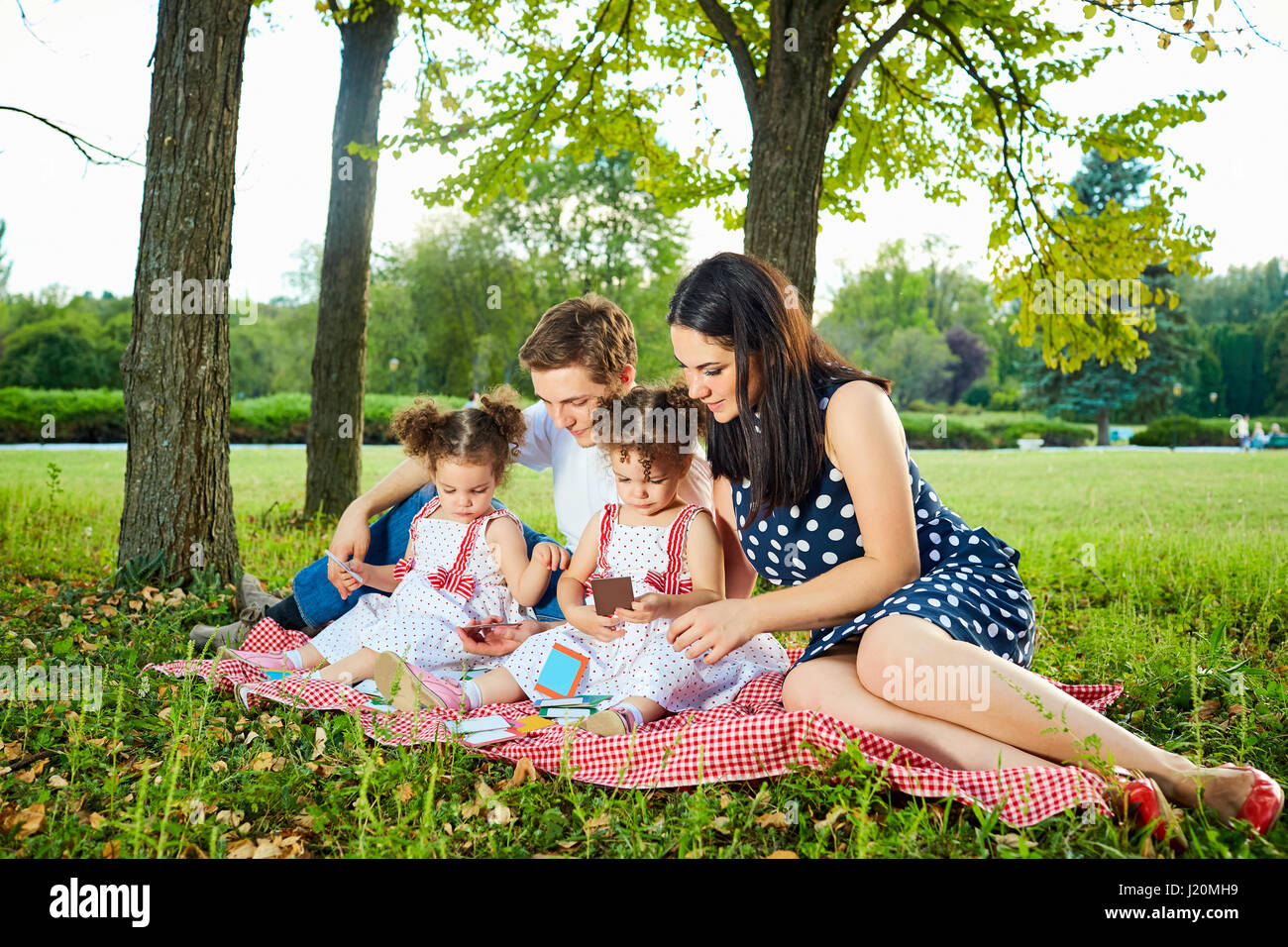 Happy family in the park summer, autumn. Parents and two daughters sitting, playing . Stock Photo