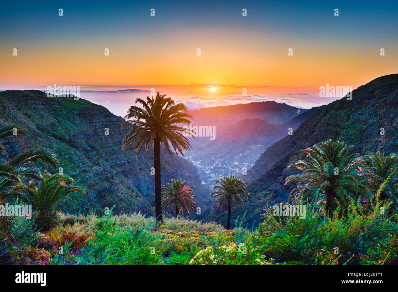 Beautiful view of amazing tropical scenery with exotic palm trees and mountain valleys above wide open sea in golden - Stock Image
