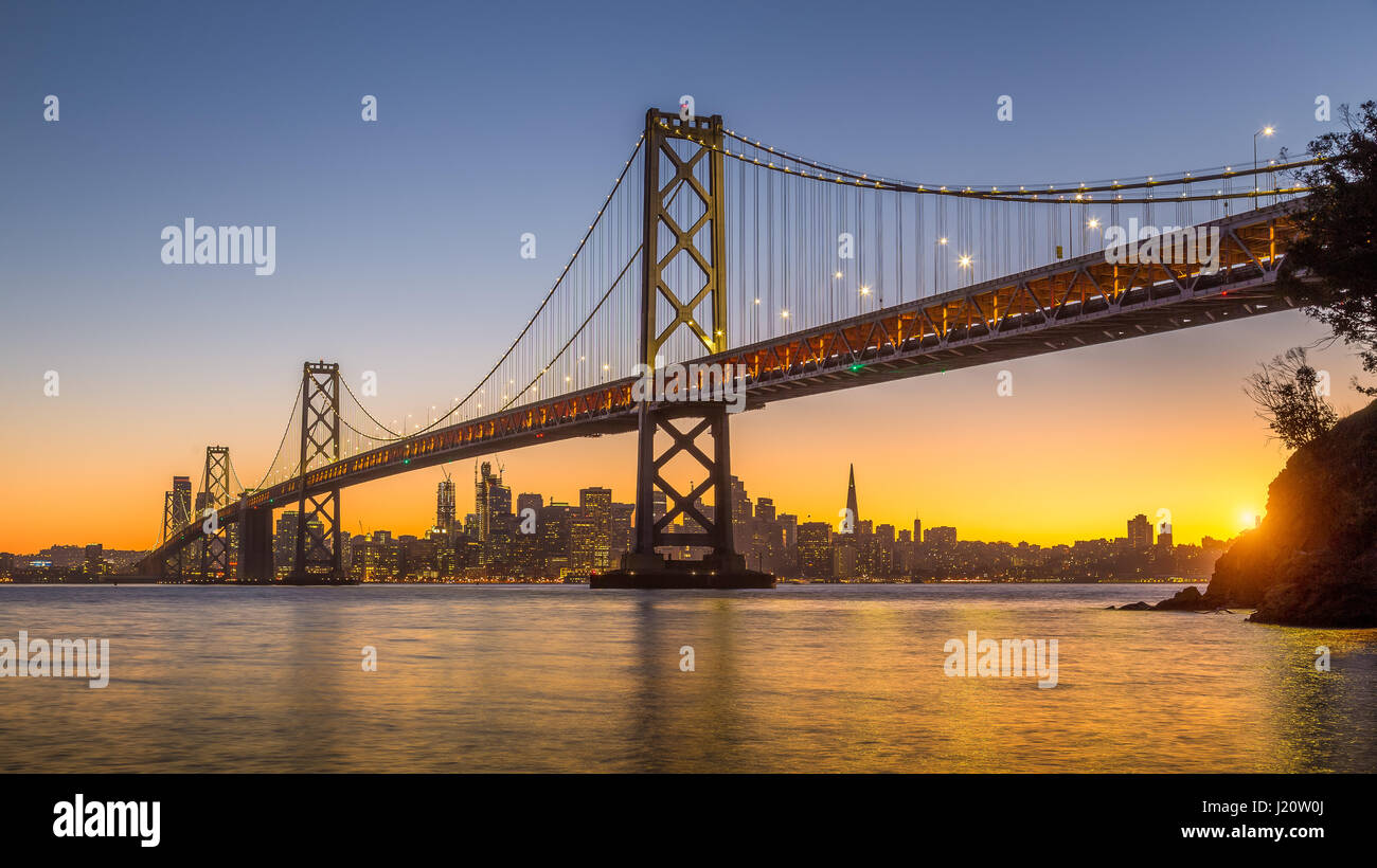 Classic panoramic view of San Francisco skyline with famous Oakland Bay Bridge illuminated in beautiful golden evening - Stock Image