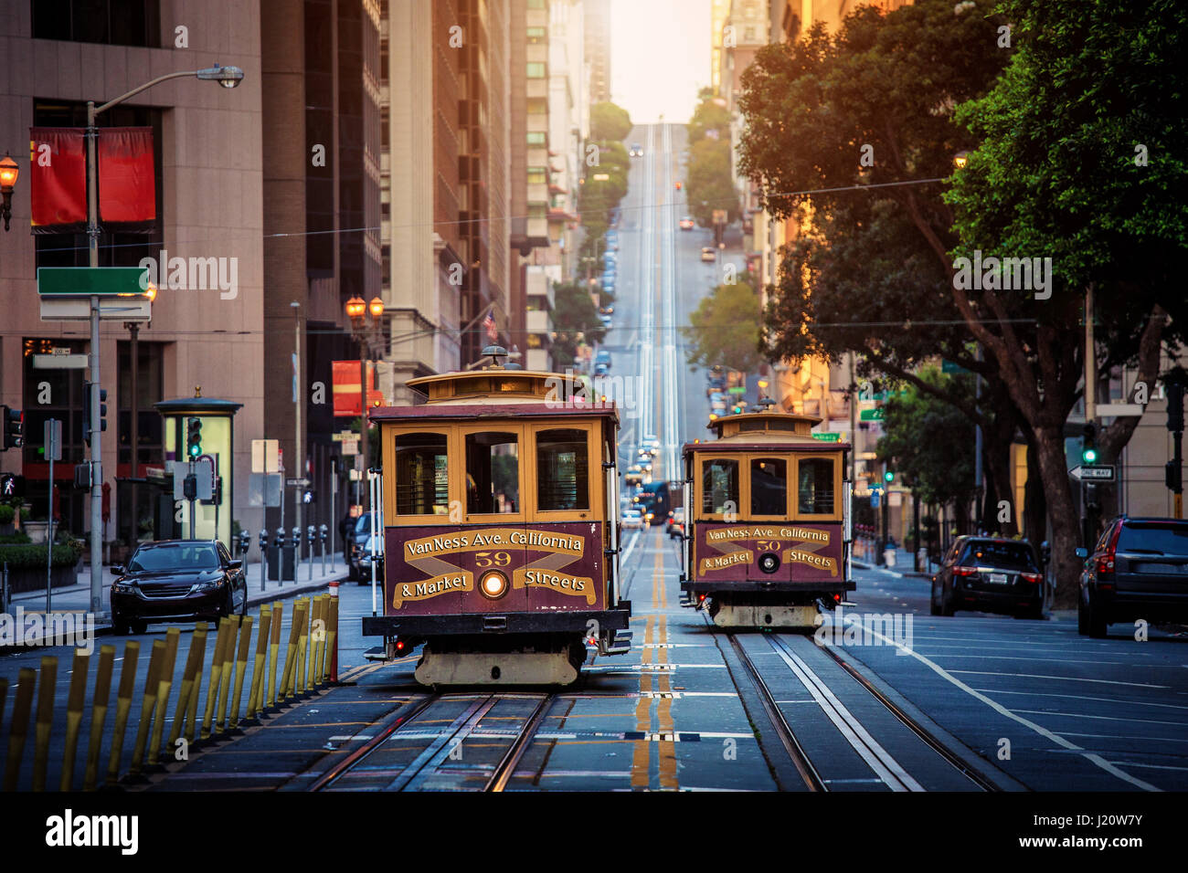 Classic view of historic traditional Cable Cars riding on famous California Street in beautiful early morning light - Stock Image