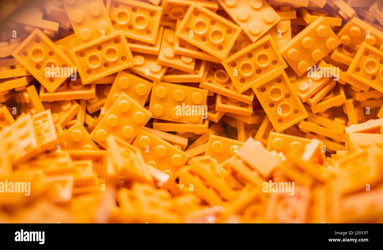 Tons of thin new 6 bump yellow Lego building blocks in a pile just waiting to form their next amazing building project - Stock Image