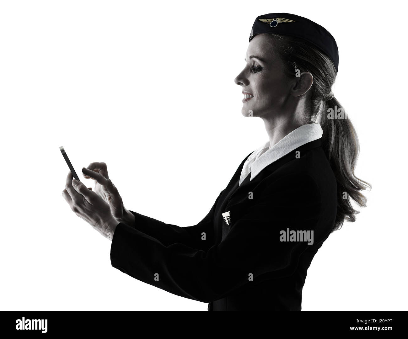 one caucasian Stewardess cabin crew  woman on the phone isolated on white background in  silhouette - Stock Image