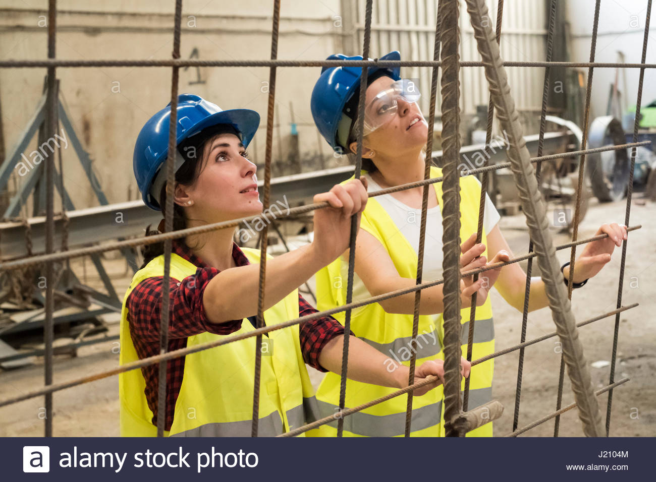 Female skilled workers in concrete factory setting up iron reinforcement - Stock Image