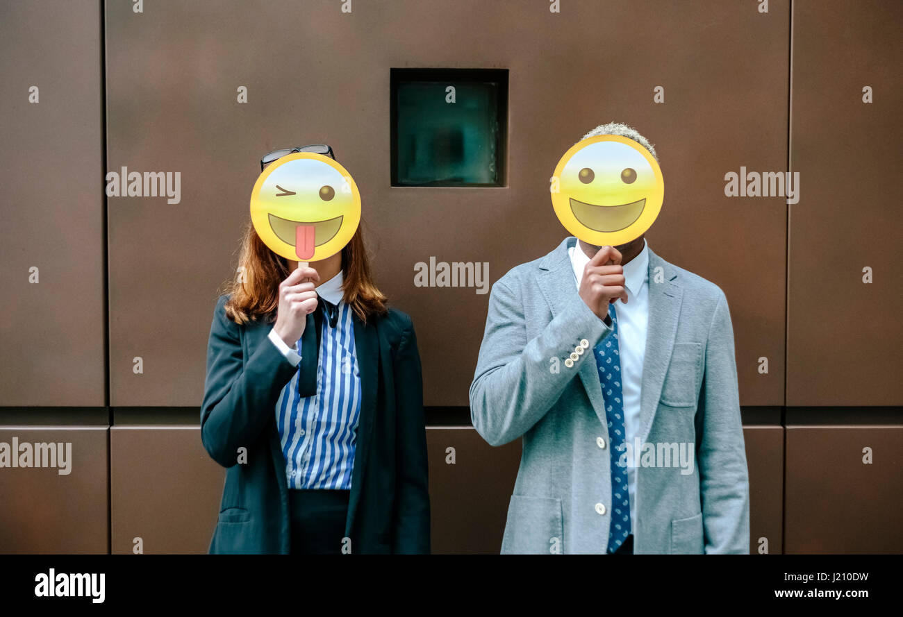 Young businessman and woman covering faces with emoji masks - Stock Image