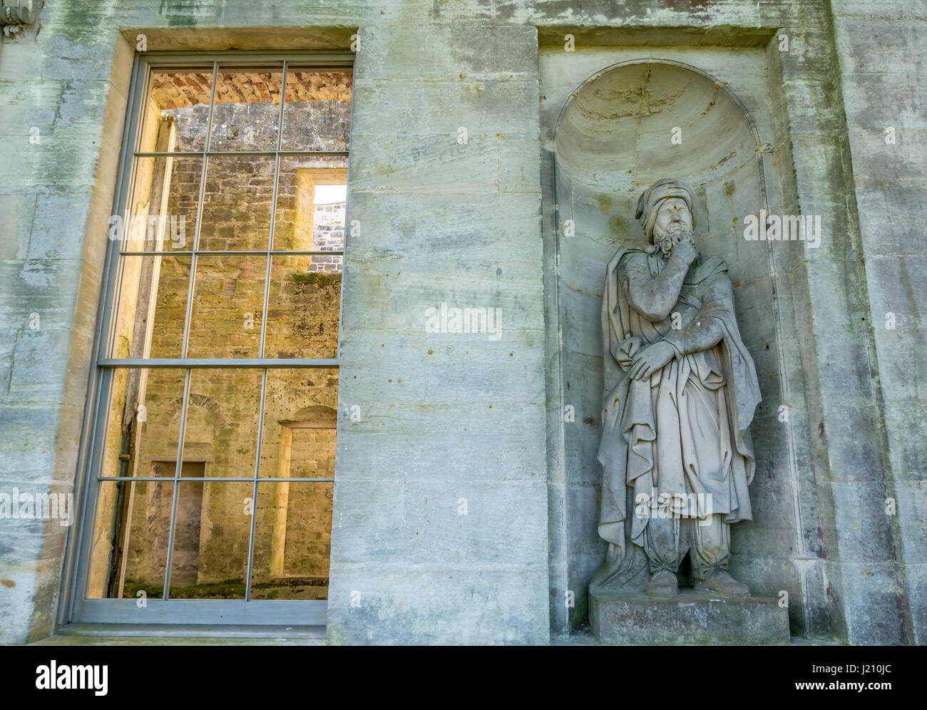 Close up stone Druid statue by Willie Jeans and sash and case window, Palladian mansion, Penicuik House, Midlothian, - Stock Image