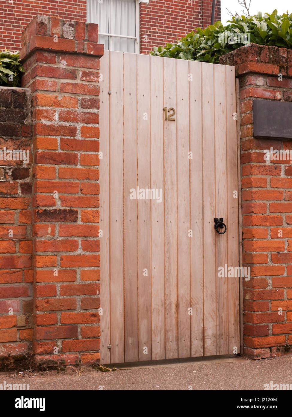 a wooden door outside closed with the number 12 on it and attached to a high wall on a house private and personal Stock Photo