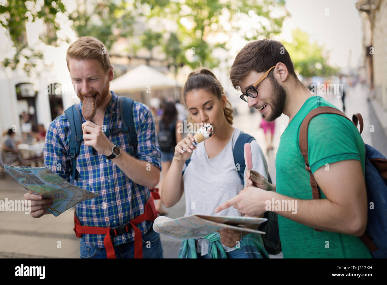 Travelling young people sightseeing and eating ice creams - Stock Image