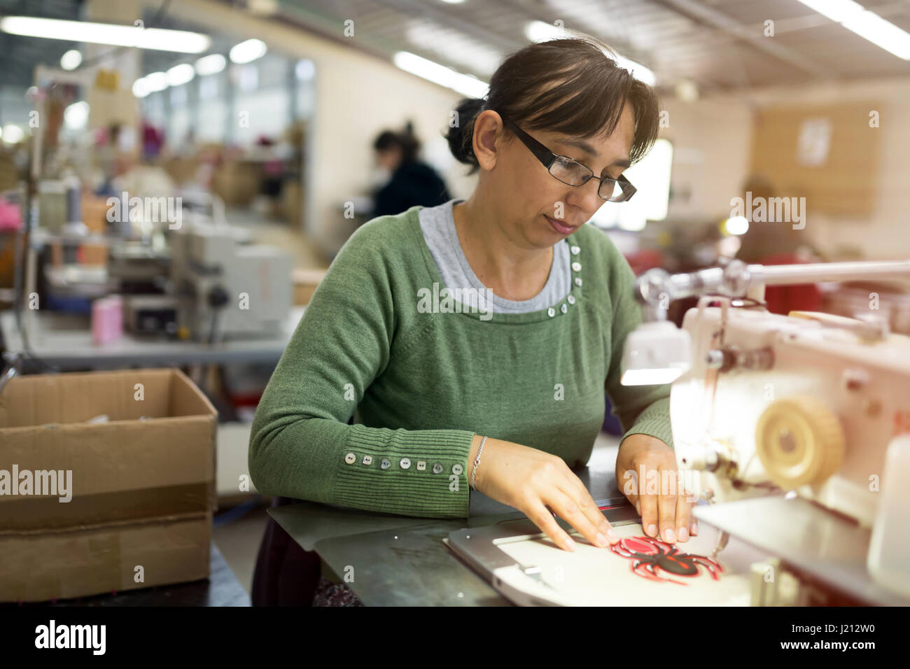 Woman working in sewing industry on machine - Stock Image