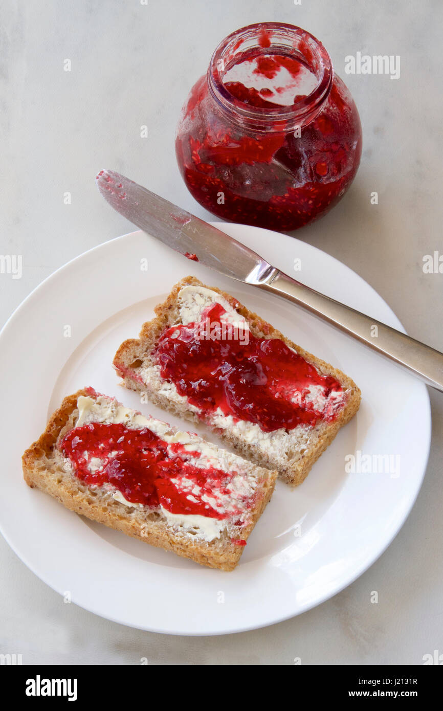 Raspberry jam on wholemeal toast. - Stock Image