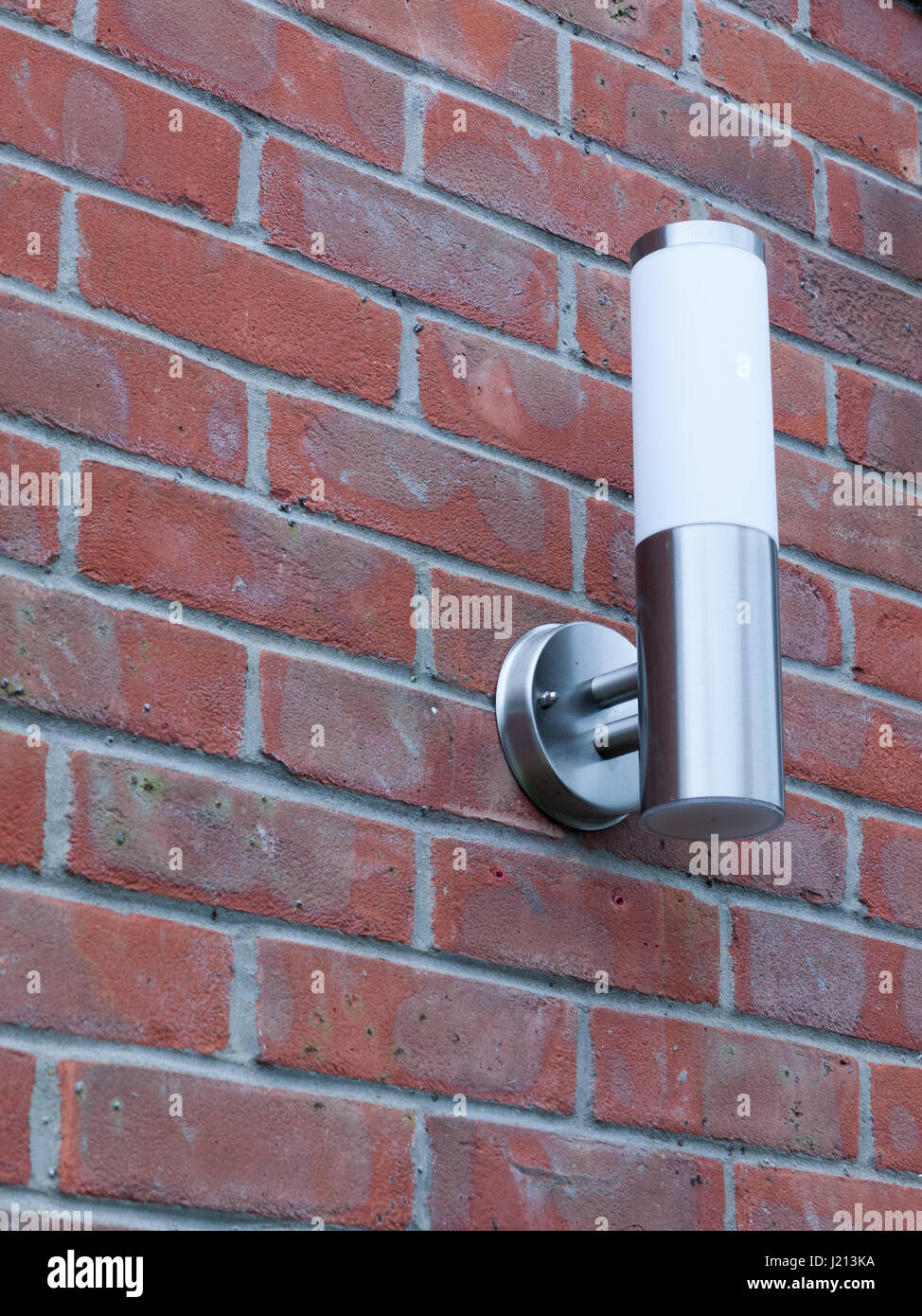 an outside metal and white modern lamp turned off not on near front door in the day light and on brick wall behind - Stock Image