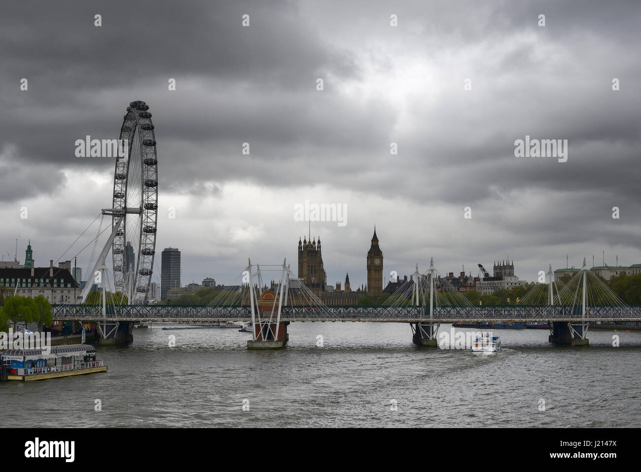 Dark clouds over the Houses of Parliament and London Eye in London - Stock Image