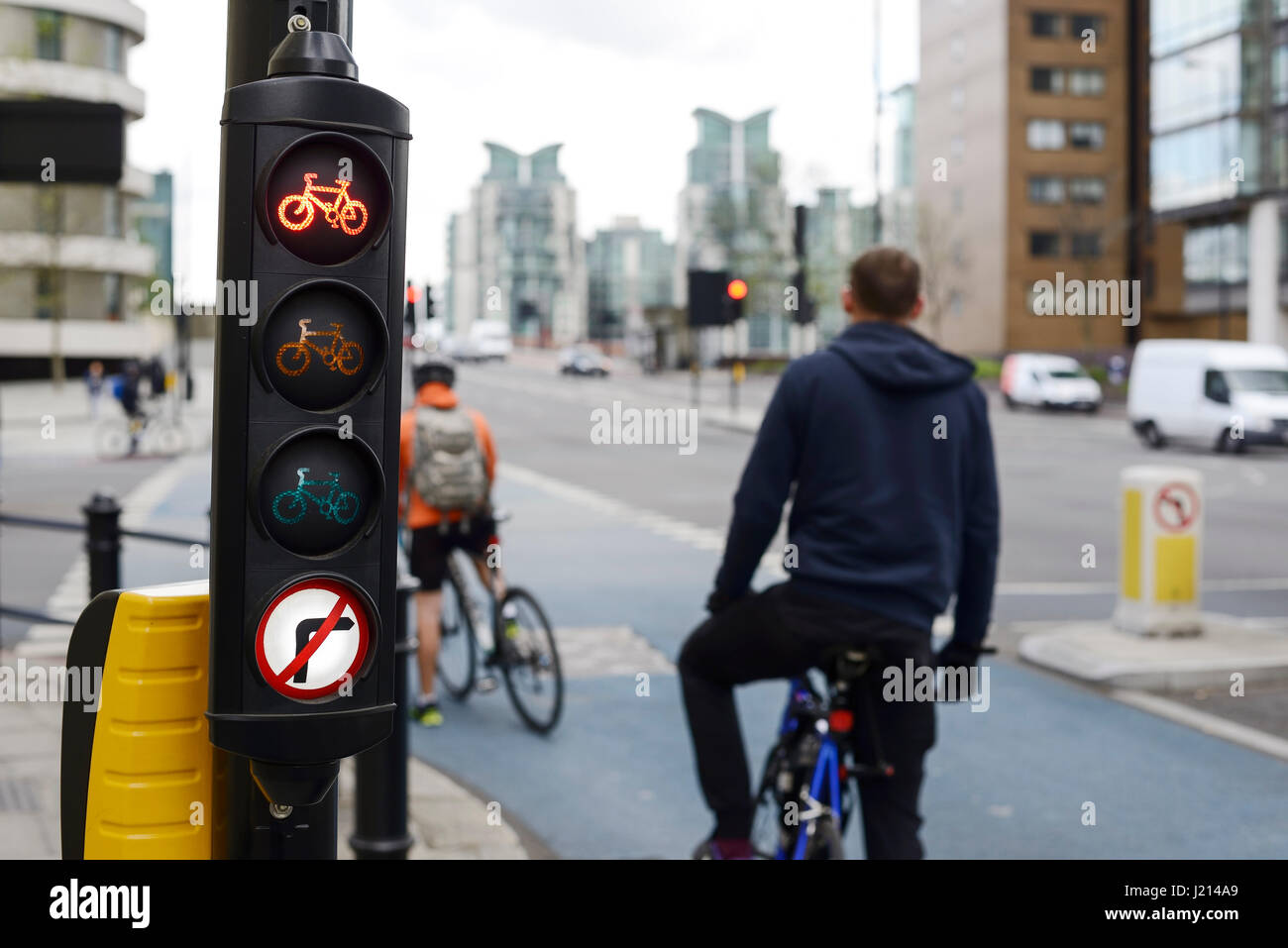 Cyclists wait at the red traffic light for a bike lane in central London UK - Stock Image