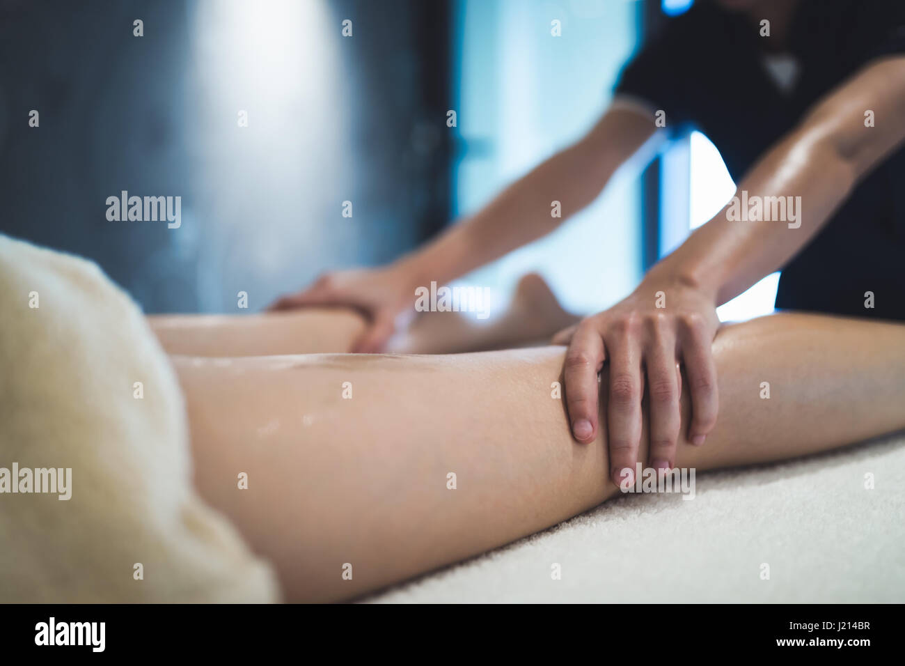 Masseur massaging masseuse during therapeutic tretment at resort - Stock Image