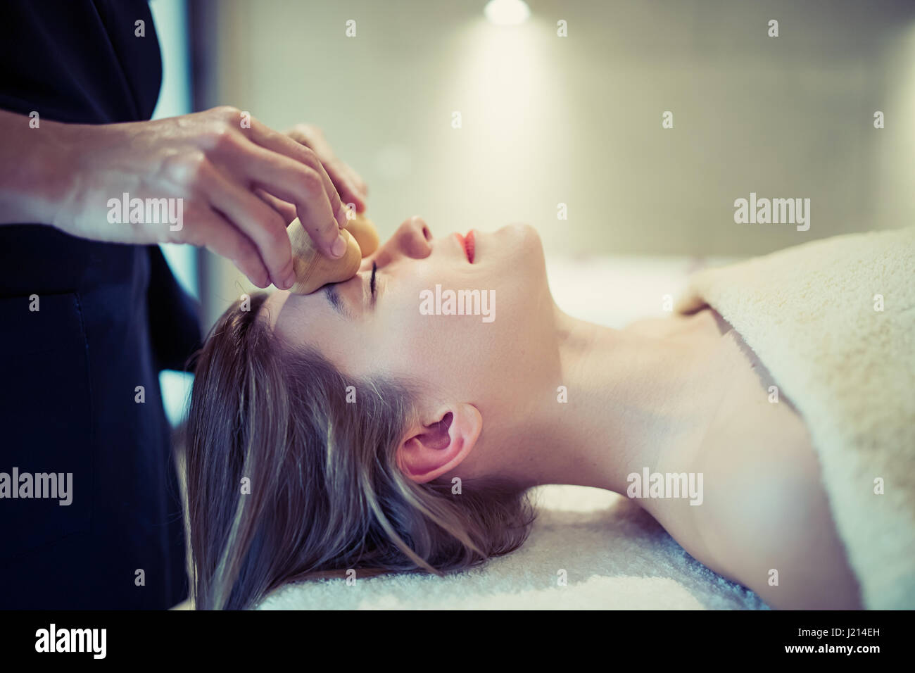 Relaxing anti stress facial massage at resort - Stock Image