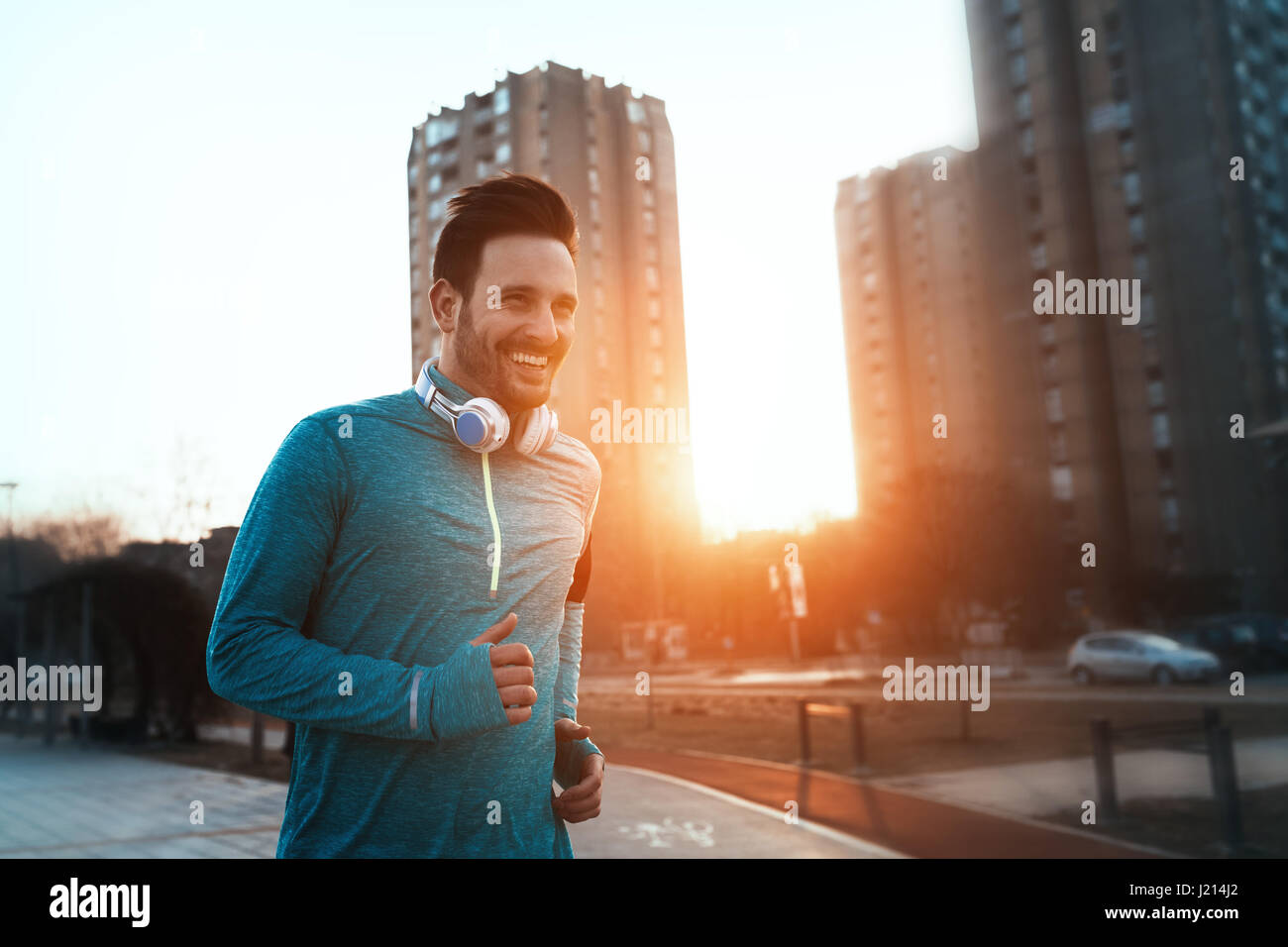 Handsome runner exercising by running and jogging  in city - Stock Image