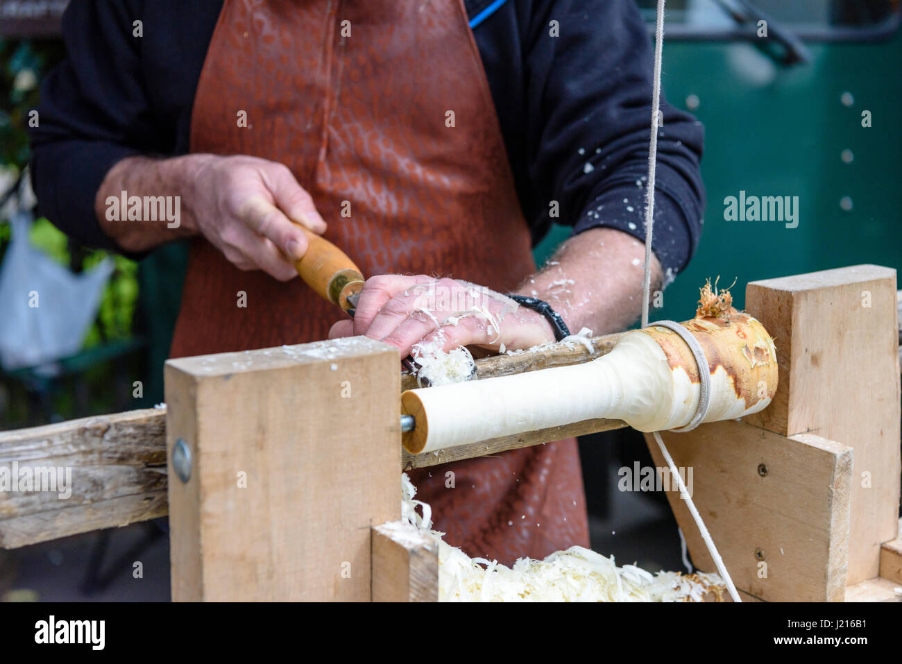 A man uses a traditional foot-operated wood turning lathe. - Stock Image