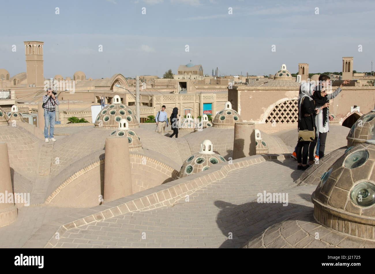 Tourists on rooftop of Sultan Amir Ahmad bathhouse in Kashan, Iran Roof domes contains convex glasses to provide - Stock Image