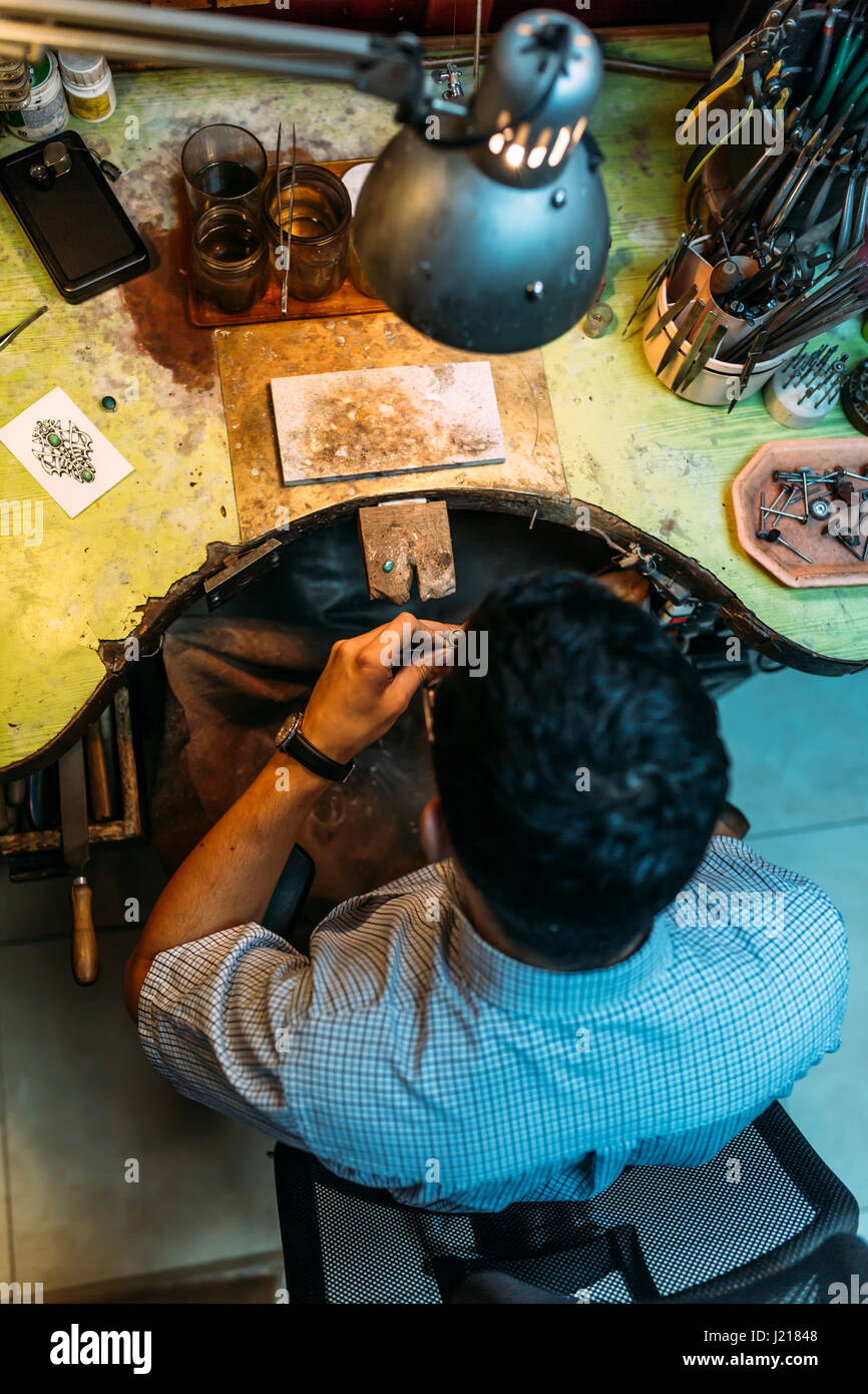 Craftsman working on workbench surrounded by his tools - Stock Image
