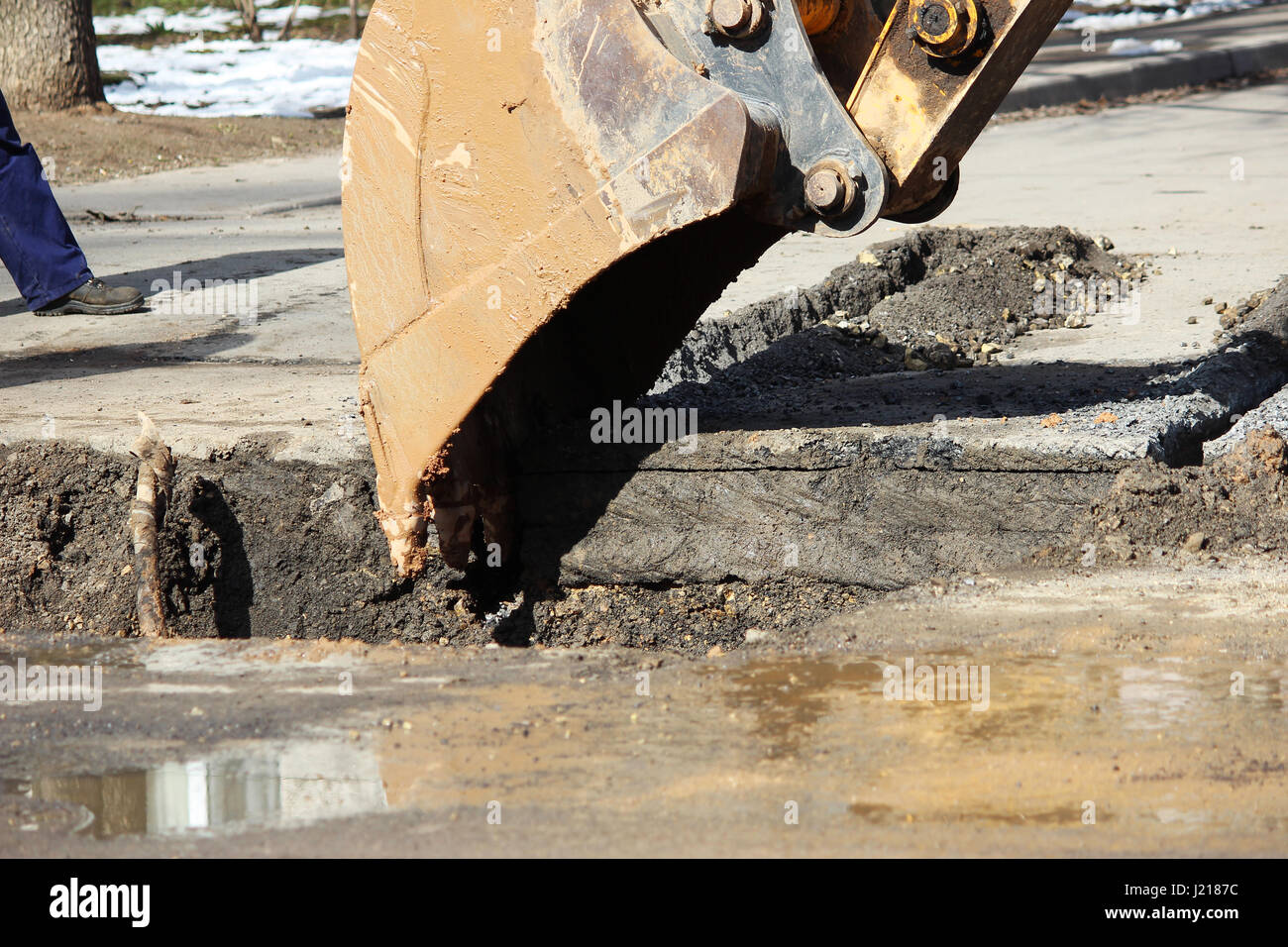 Opening the road surface when eliminating accidents under the ground. Using of a tractor with a special attachment - Stock Image