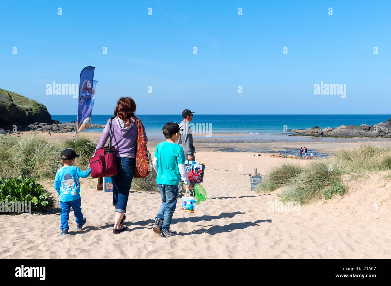 family on the beach at poldhu cove in cornwall, england, uk - Stock Image