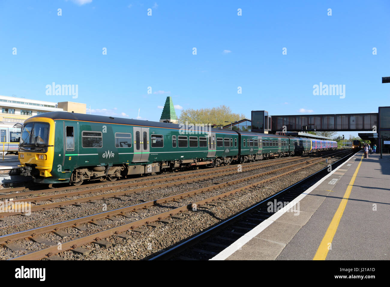 Class 165 turbo diesel multiple unit train in Great Western Railway green livery at Oxford station with passenger - Stock Image