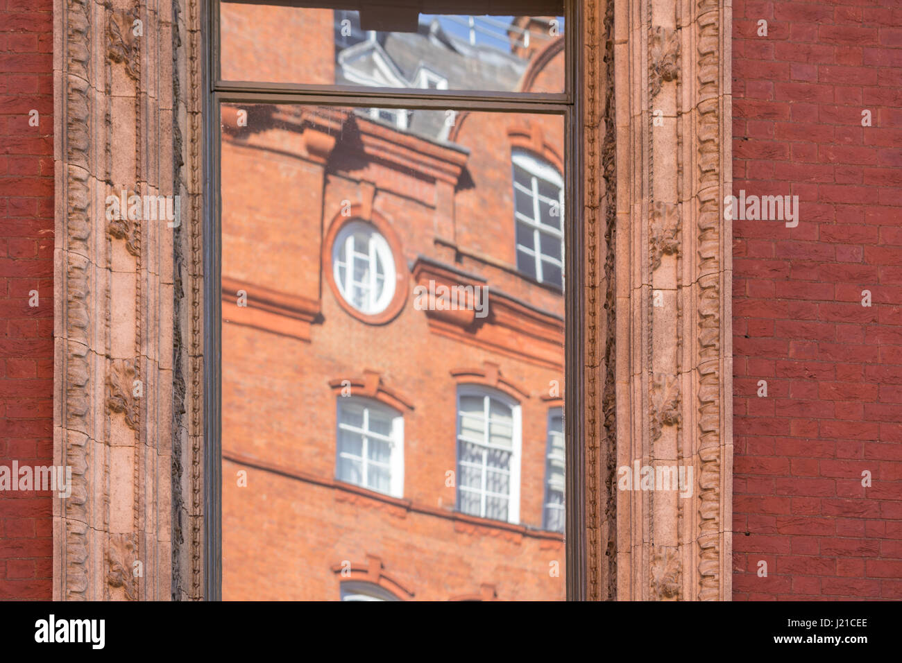 reflection of an old brick building in London in an a window with elaborate molding, London England, UK - Stock Image