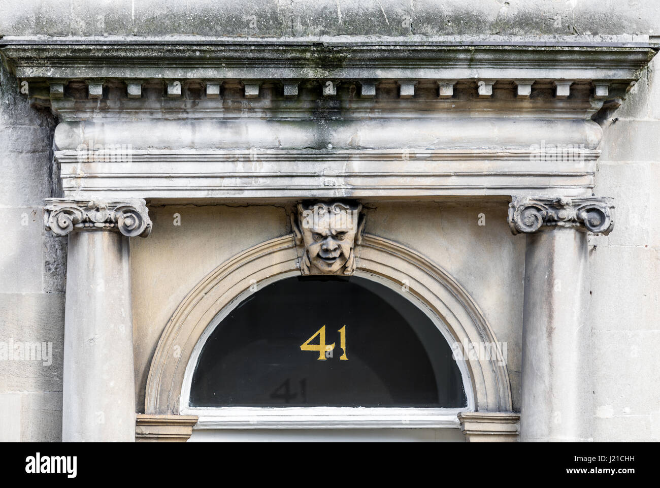 Door captial with face, Doric columns and pediment in London England, UK - Stock Image
