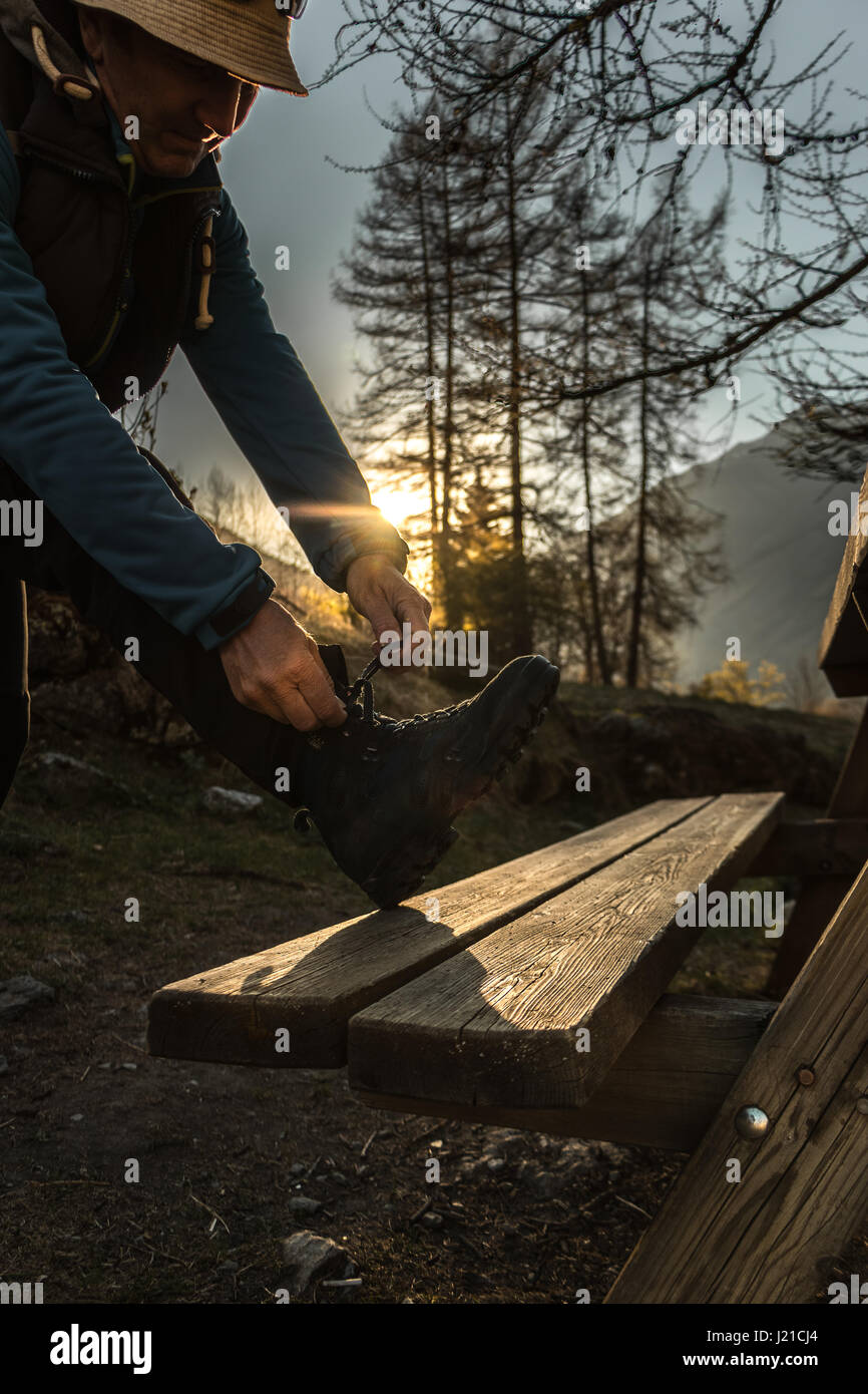 A man adjusting his hiking boots to go for a mountain hike as the sunrise or sunset in the mountains alpine landscape - Stock Image