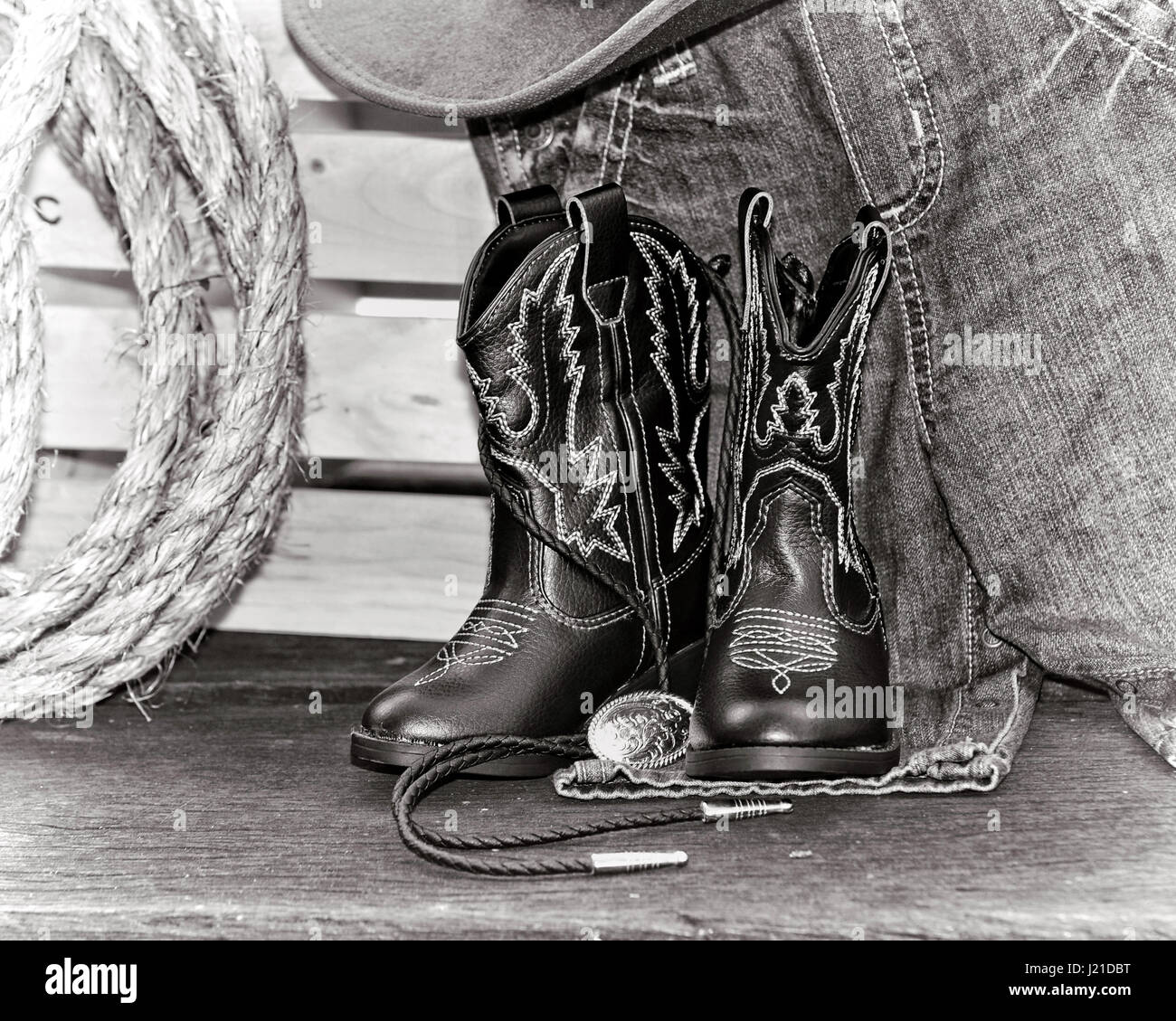 Cowboy boots with bolo tie sitting on blue jeans - Stock Image