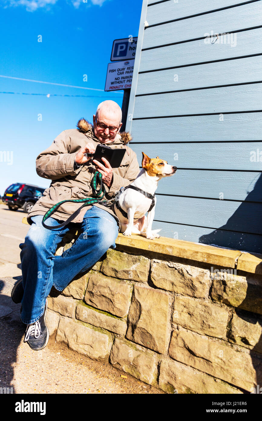Man on phone with dog man using phone dog waiting patiently man stopped to use phone old man using smartphone UK - Stock Image