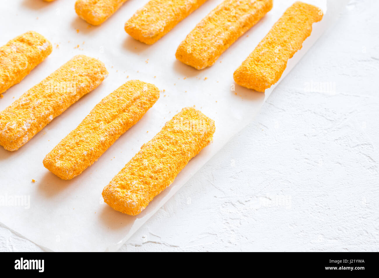 Frozen fish sticks, fish fingers on paper and white background, copy space. Convenience food, seafood, fish food Stock Photo
