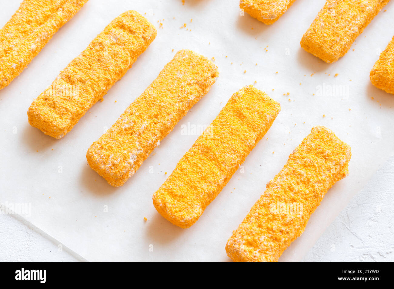 Frozen fish sticks, fish fingers on paper and white background, copy space. Convenience food, seafood, fish food - Stock Image