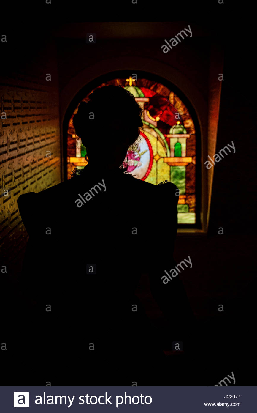 Silhouette of Victorian woman in front of a stained glass window - Stock Image