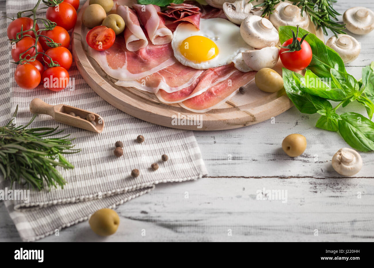 Healthy Mediterranean breakfast groceries: fried eggs, ham, vine tomatoes, mushrooms, basil, olives, rosemary on - Stock Image
