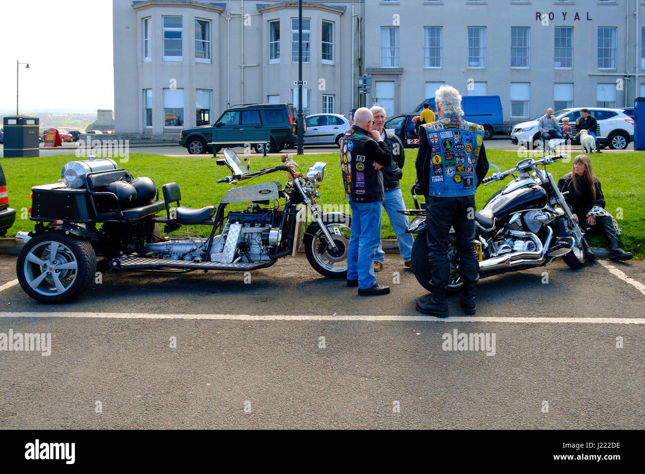Elderly Bikers on West Cliff at Whiby Goth Week-end one with a high powered motorcycle, the other with a lrge Ford - Stock Image