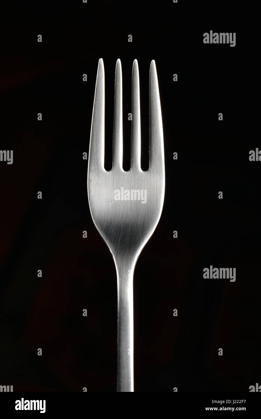 fork in a black background - Stock Image