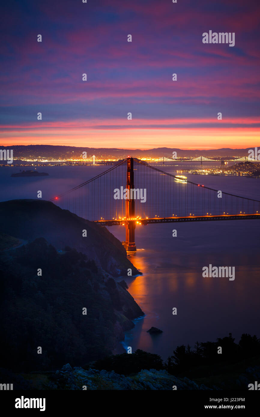 View of Golden Gate Bridge from Hawk Hill at Sunrise with Dramatic Clouds - Stock Image