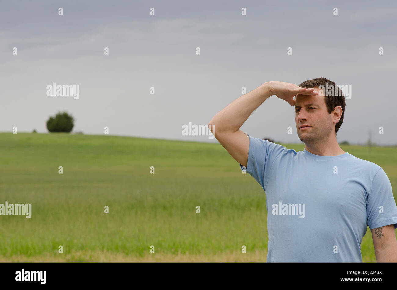 Man with hand on his forehead looking off into the distance with a grassy field in the background. - Stock Image