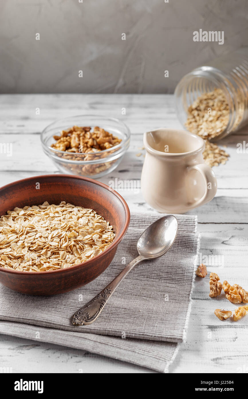 Oat flakes in brown clay bowl ready to cook, scattered oat flakes, walnuts, jug with milk and spoon on the light Stock Photo