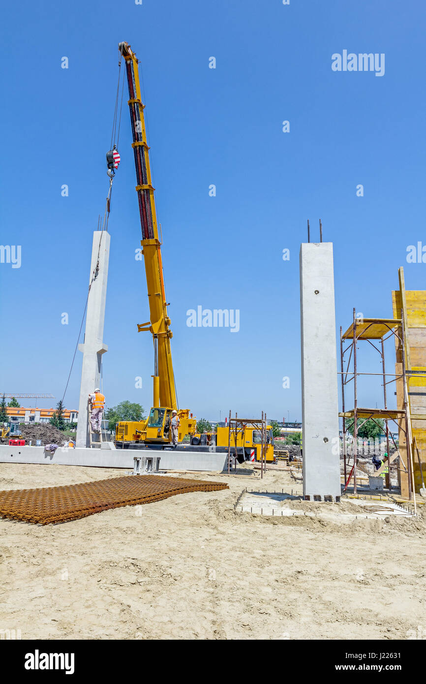 Mobile crane is operating and worker is assembly concrete joist in high place. Height worker is placing truss on - Stock Image