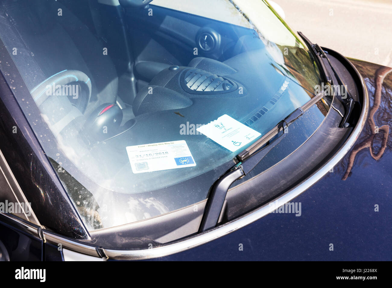 disabled parking badge in car window free car park space for badge holders UK England disability parking badge - Stock Image